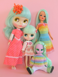 Fyra olika dockor: Neo Blythe, Middie Blythe, Sindy samt Emerald Witch på golvet.